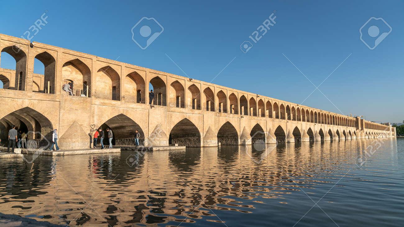 Isfahan, Iran - May 2019: Iranian people on Allahverdi Khan Bridge also known as Si-o-se-pol Bridge, one of the oldest bridges of Isfahan - 164356041