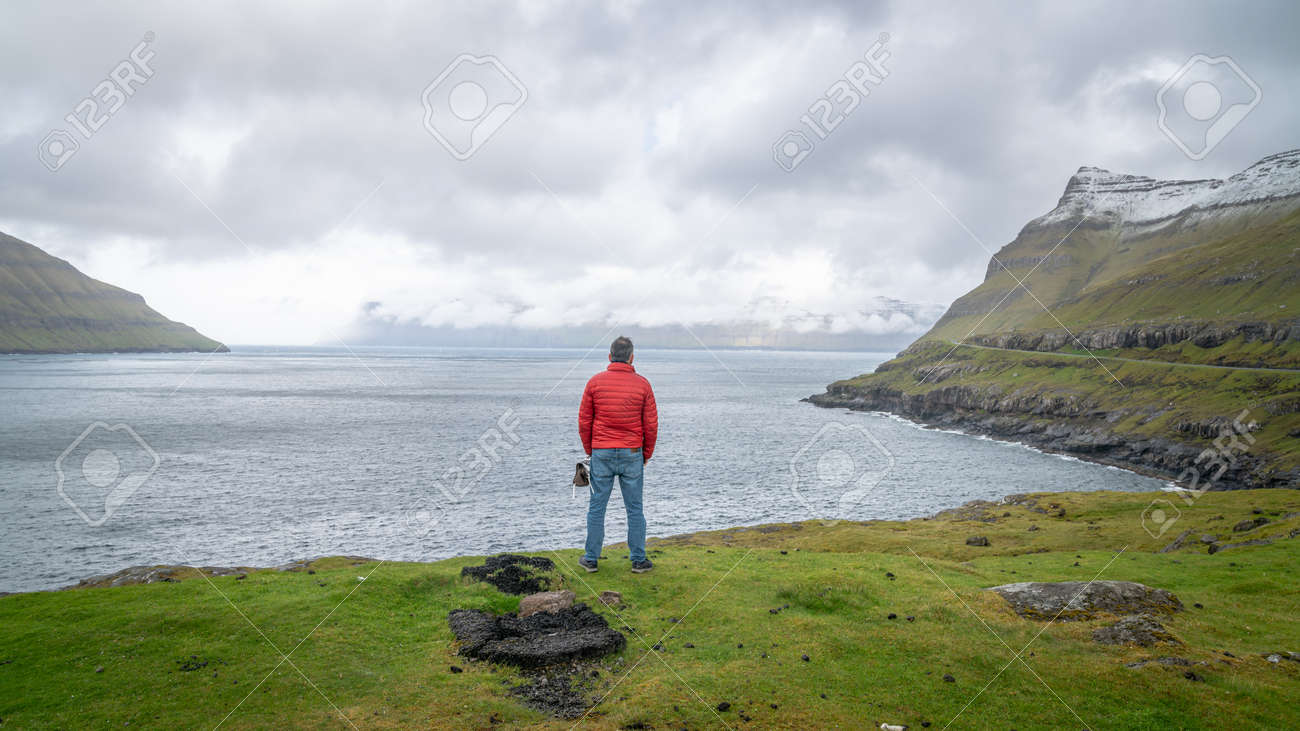 Torshavn, Faroe Islands - August 2019: Unidentified man looking at the dramatic landscape in Faroe Islands, Denmark - 164356039