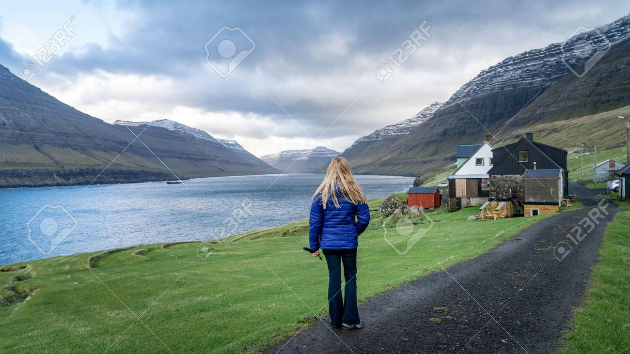 Vidareidi, Faroe Islands - August 2019: Unidentified woman looking at the dramatic landscape in Faroe Islands, Denmark - 164356034