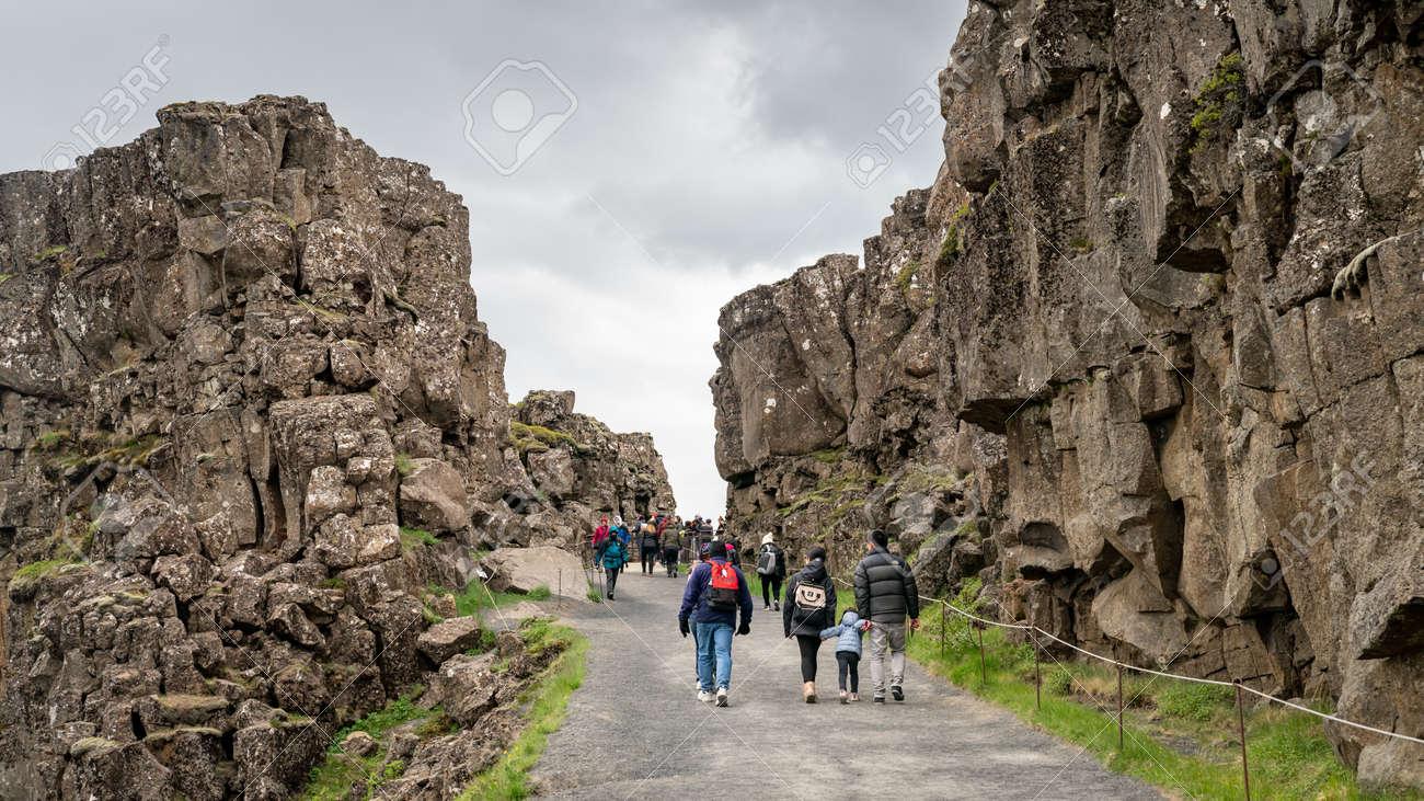 Thingvellir, Iceland - August 2019: Tourists walking along Thingvellir National Park with creek of tectonic plates - 164356030