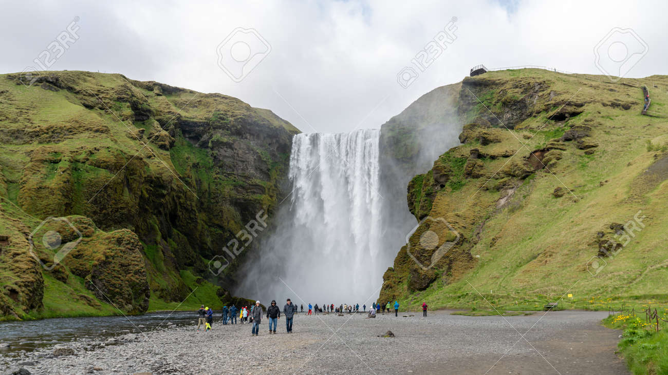 Skogar, Iceland - August 2019: Skogafoss waterfall with tourists visiting in Skogar, south of Iceland. Majestic nature of Iceland. - 164356028
