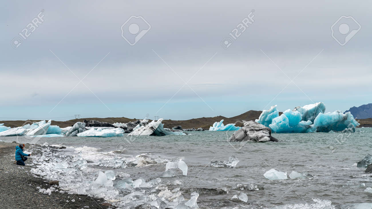 Unidentified woman taking a photo of icebergs in Jokulsarlon glacier lagoon formed with melting ice, Iceland, global warming and climate change concept - 164356027
