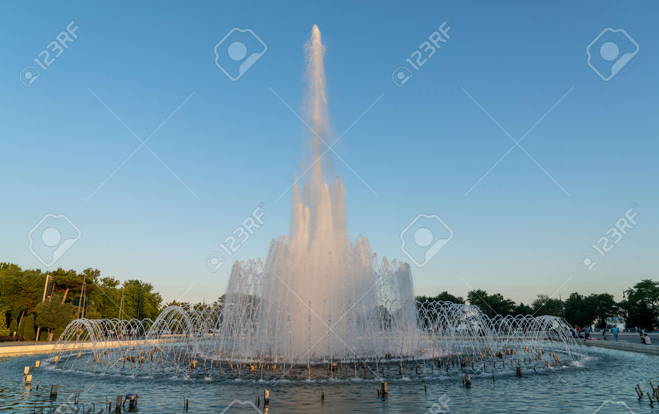 Baku, Azerbaijan - July 2019: Fountain in Baku National Seaside Park in front of the parliament building in the evening - 164356026