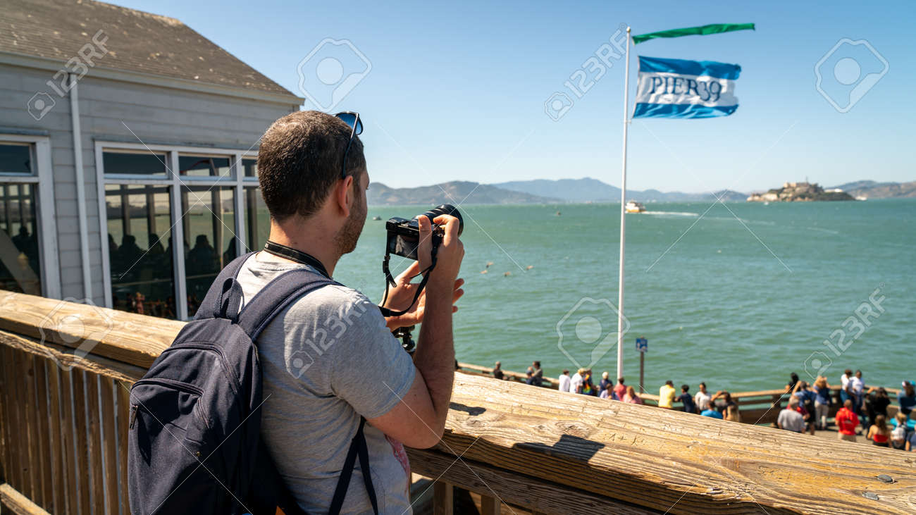 San Francisco, California, USA - August 2019: Man taking photos of Alcatraz Iceland standing in Pier 39 the fisherman's wharf - 164356015
