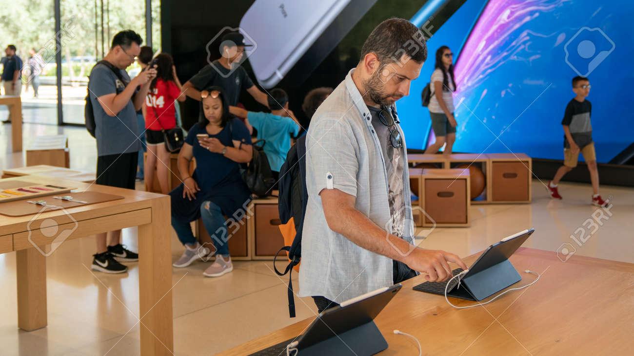 Cupertino, CA, USA - August 2019: Man examining an iPad in Apple Store in Cupertino, Apple Headquarters infinite loop - 164356008