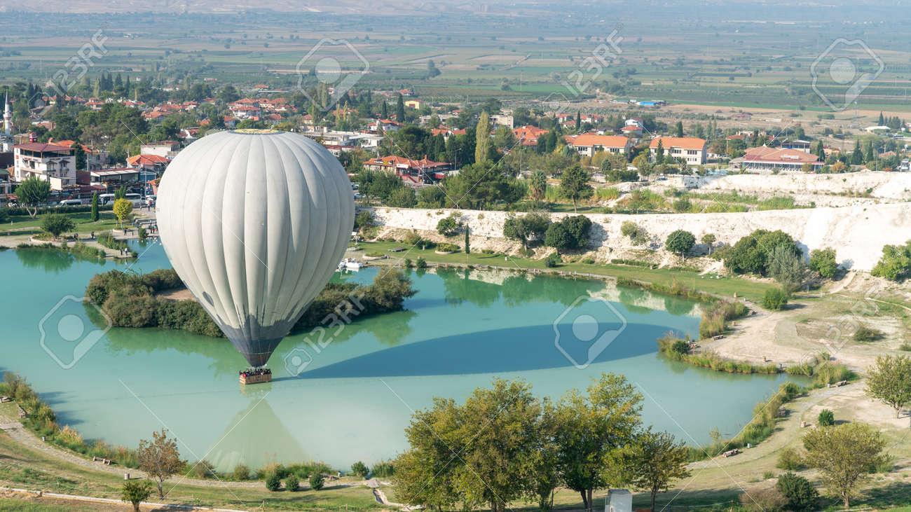 Denizli, Turkey - October 2019: Hot air balloon touching the pool near Pamukkale travertine - 164355963