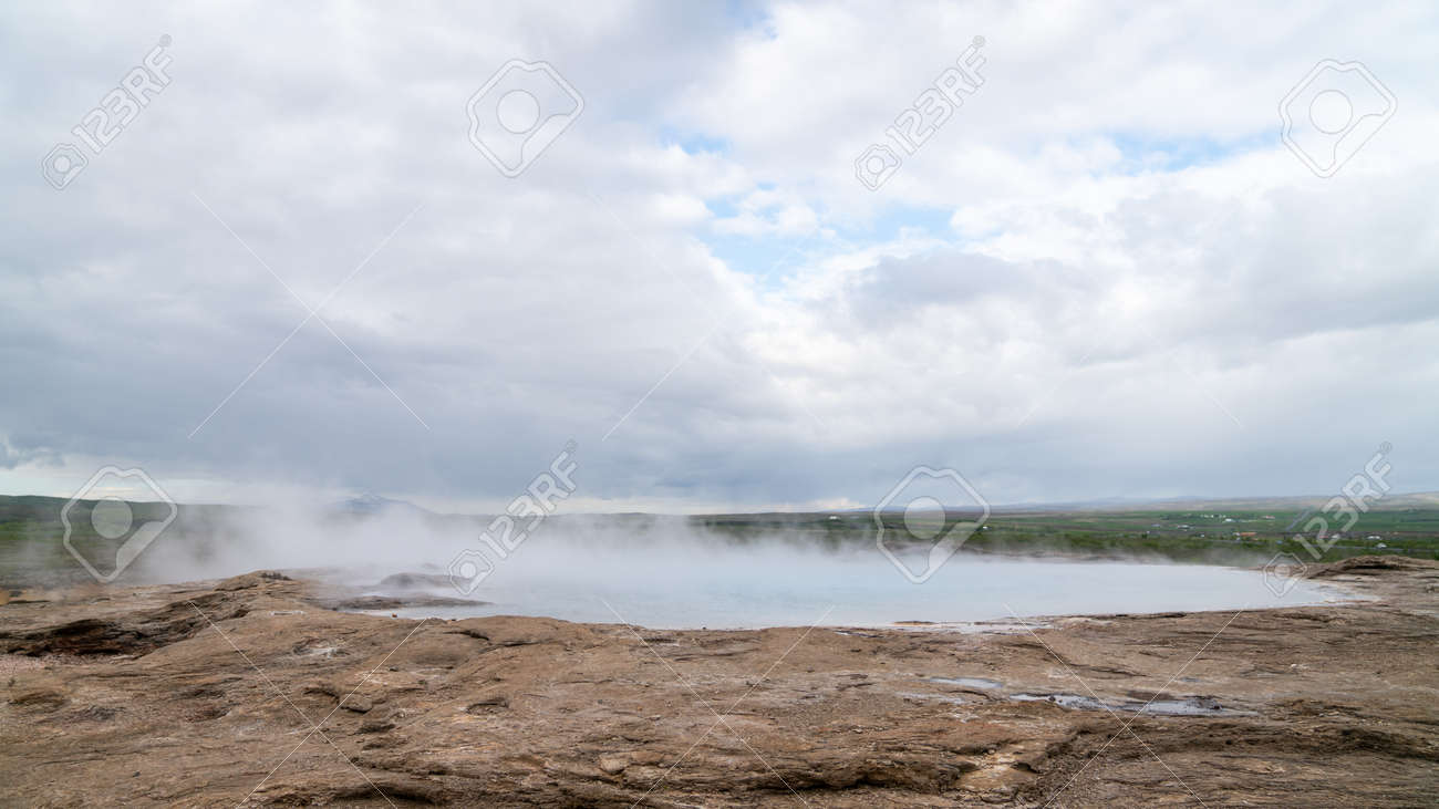 Strokkur geothermal landscape in Iceland with hot water and smoke, Strokkur, Iceland. High concentration of volcanoes is often an advantage in the generation of geothermal energy in Iceland - 164386219