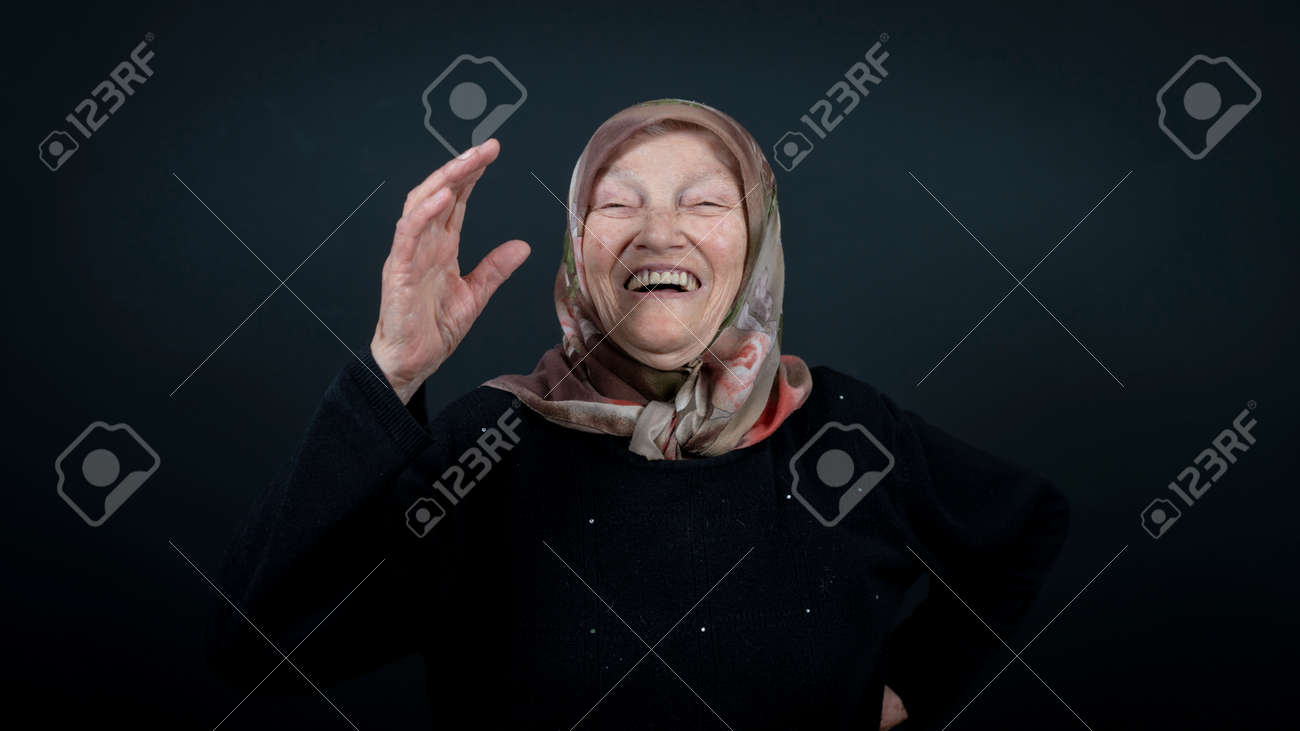 Portrait of a Turkish senior muslim woman with black background. She is very happy and laughing. - 172150636