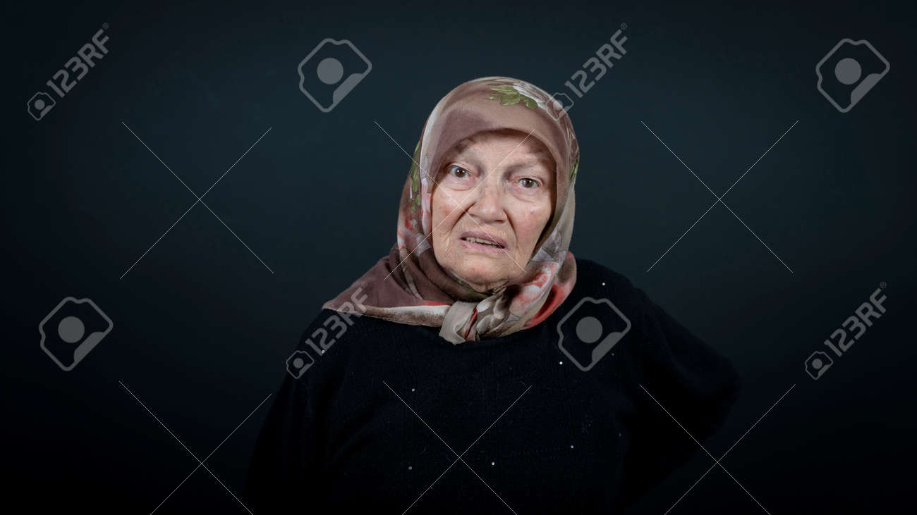 Portrait of a Turkish senior muslim woman with black background. She is nervous, tense and unhappy - 172150640