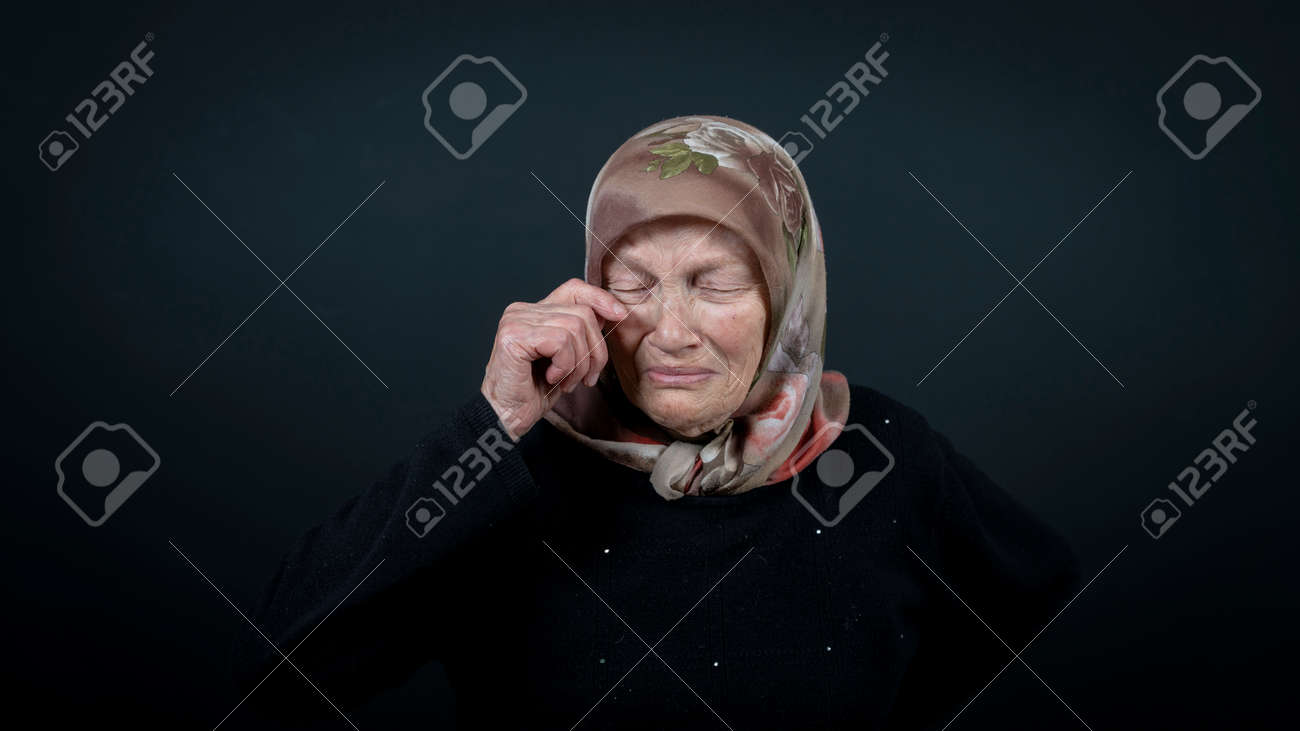 Portrait of a Turkish senior muslim woman with black background. She is sad, unhappy and crying. - 172150645
