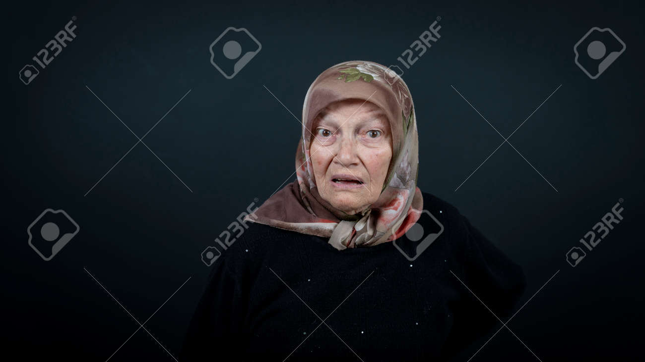 Portrait of a Turkish senior muslim woman with black background. She is surprised, scared and shocked. - 172150647