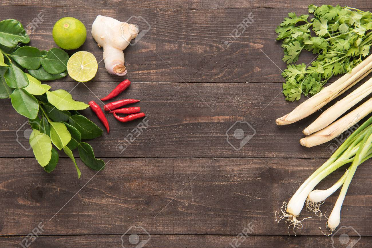 Kaffir lime leaves, coriander or cilantro, Ginger, lemon, lemon grass, red chilli and green onions on wooden background. Overhead view. - 42055757