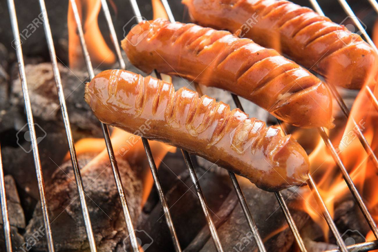 Grilling sausages over flames on the grill. - 43493711