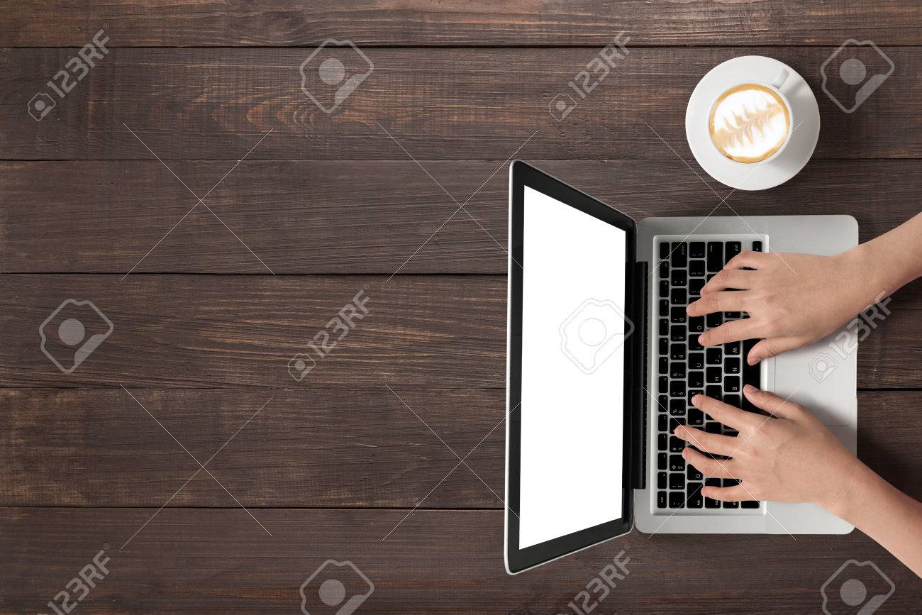 Using laptop and a cup of coffee on wooden background. - 55643311