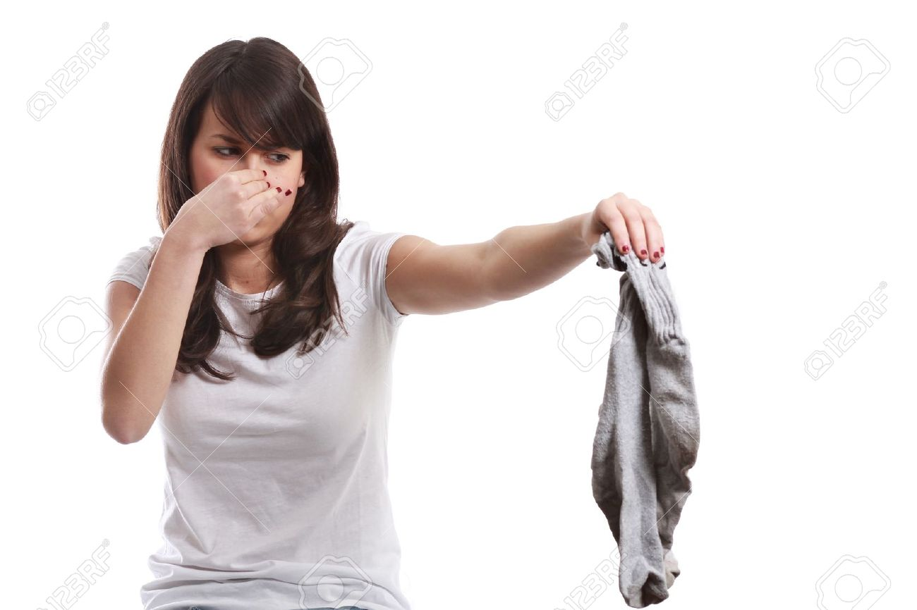 Young girl disgusted expression for stinking socks   On white   Bad smell concept Stock Photo - 12727574
