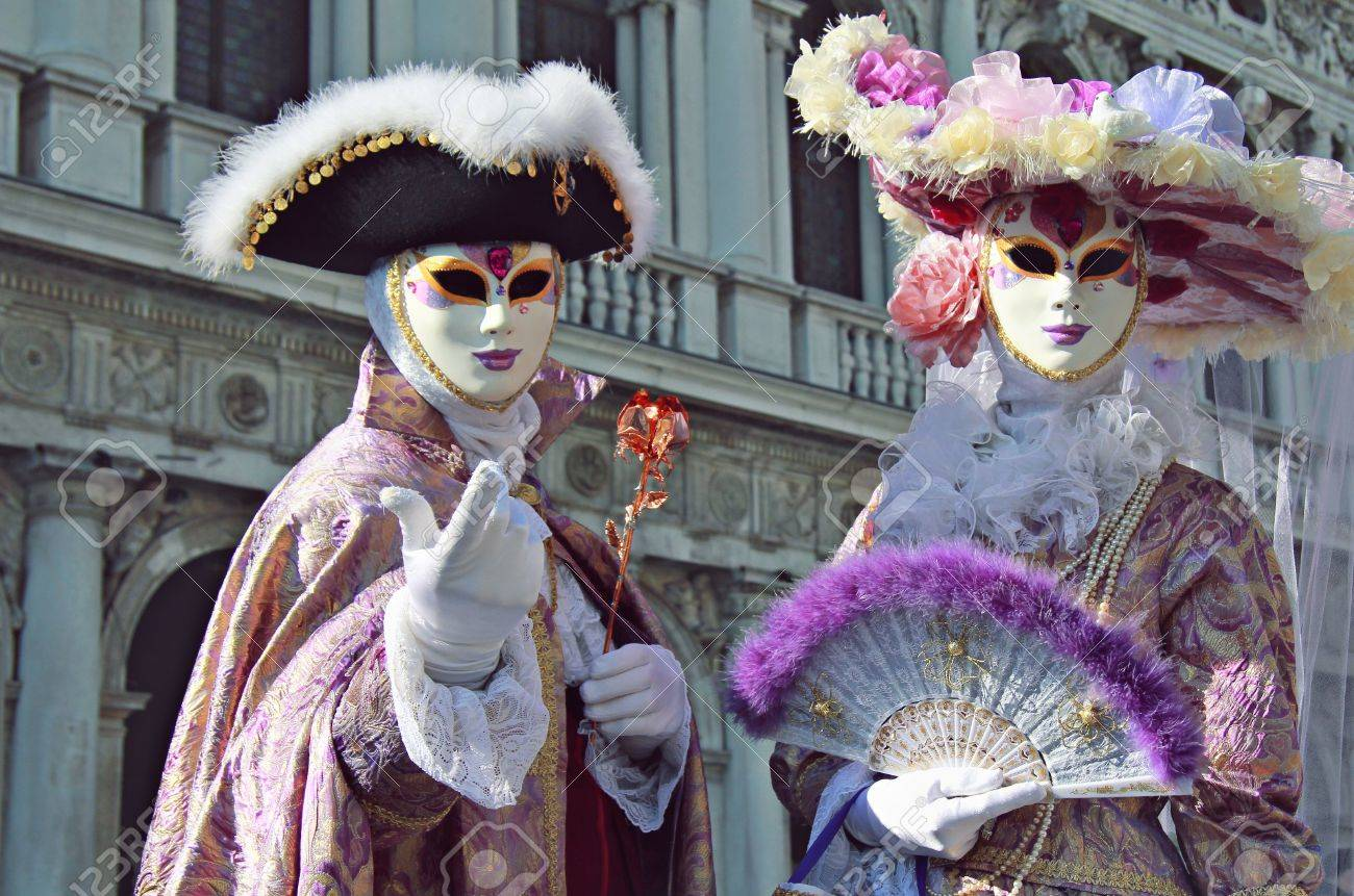 Beautiful noble couple in elegant silk dress  . Man is calling with finger gesture .Venice carnival 2012 . Stock Photo - 12797697