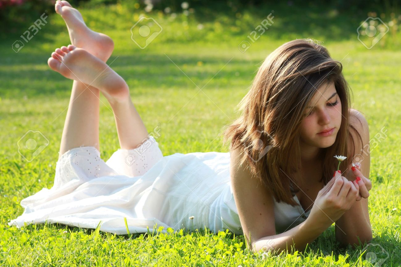 pretty young girl is tearing petals from a daisy lying on grass