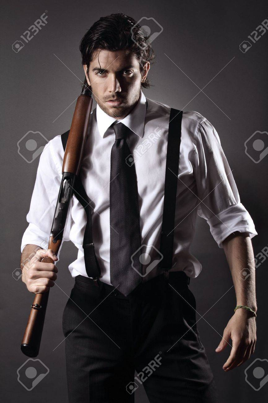 very attractive fashion model dressed like a gangster with shotgun