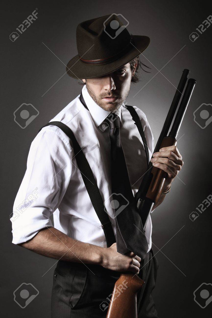 Fashion model dressed like a gangster poses with shotgun and hat Stock  Photo - 19502013 91d0f151e74