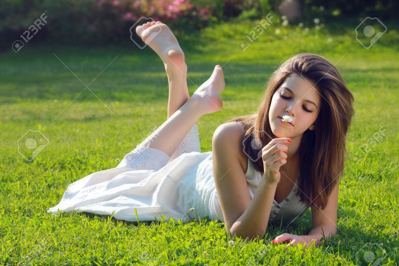young feet Stock Photo - Pretty young girl with a daisy in hand, lying on grass with bare feet . Purity and relax conceptual