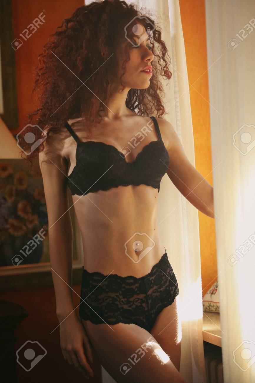 f3c201c1d453 Foto de archivo - Presentación modelo atractiva en ropa interior por la  ventana. Luz natural caliente