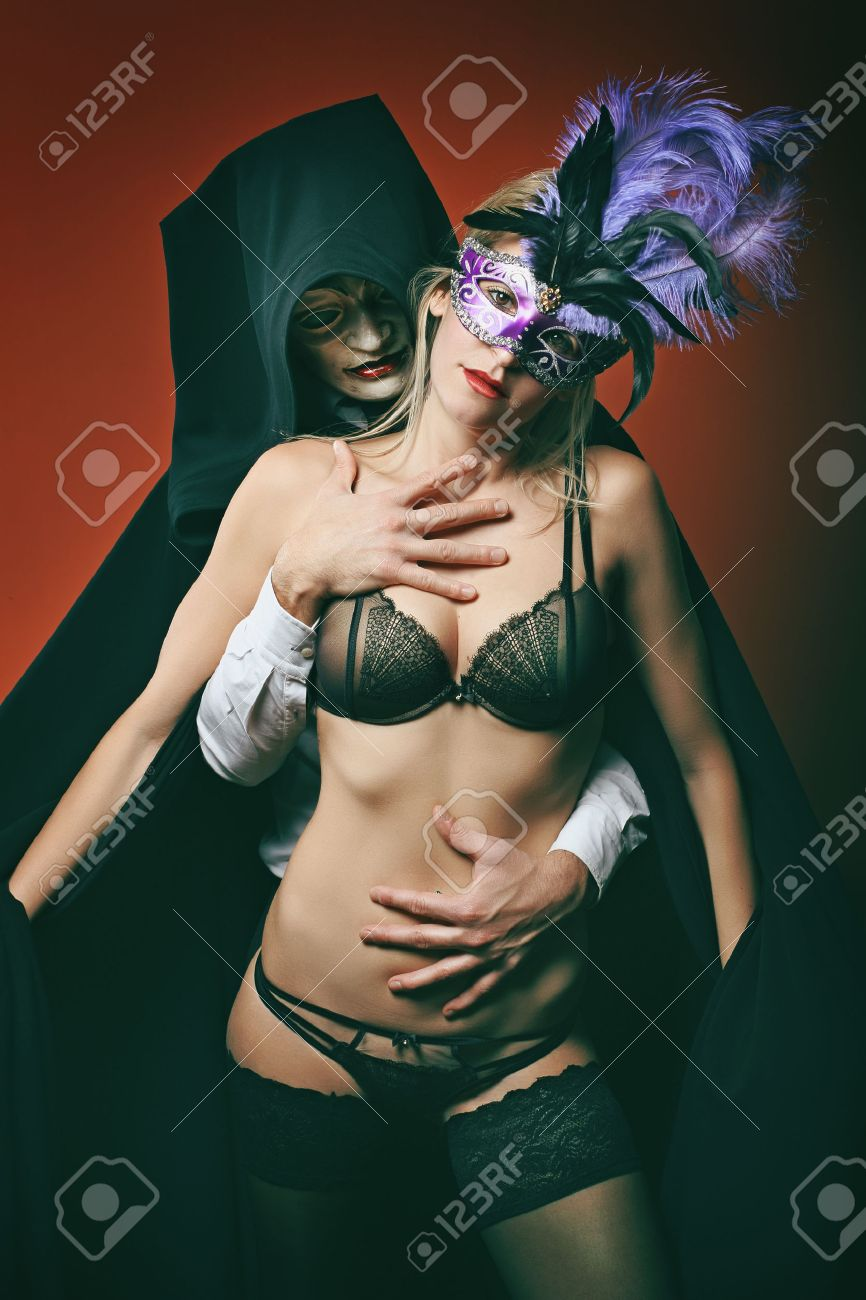 957b4127d10ae Beautiful woman posing with venetian mask and mysterious dark man . Venice  masquerade Stock Photo -