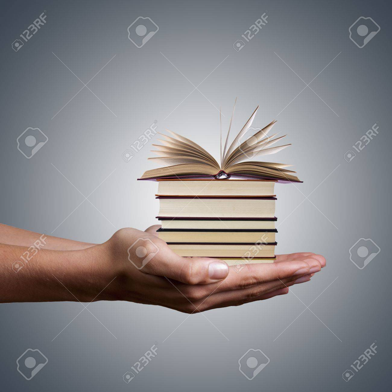 hands holding stacked books on white background - 18394457