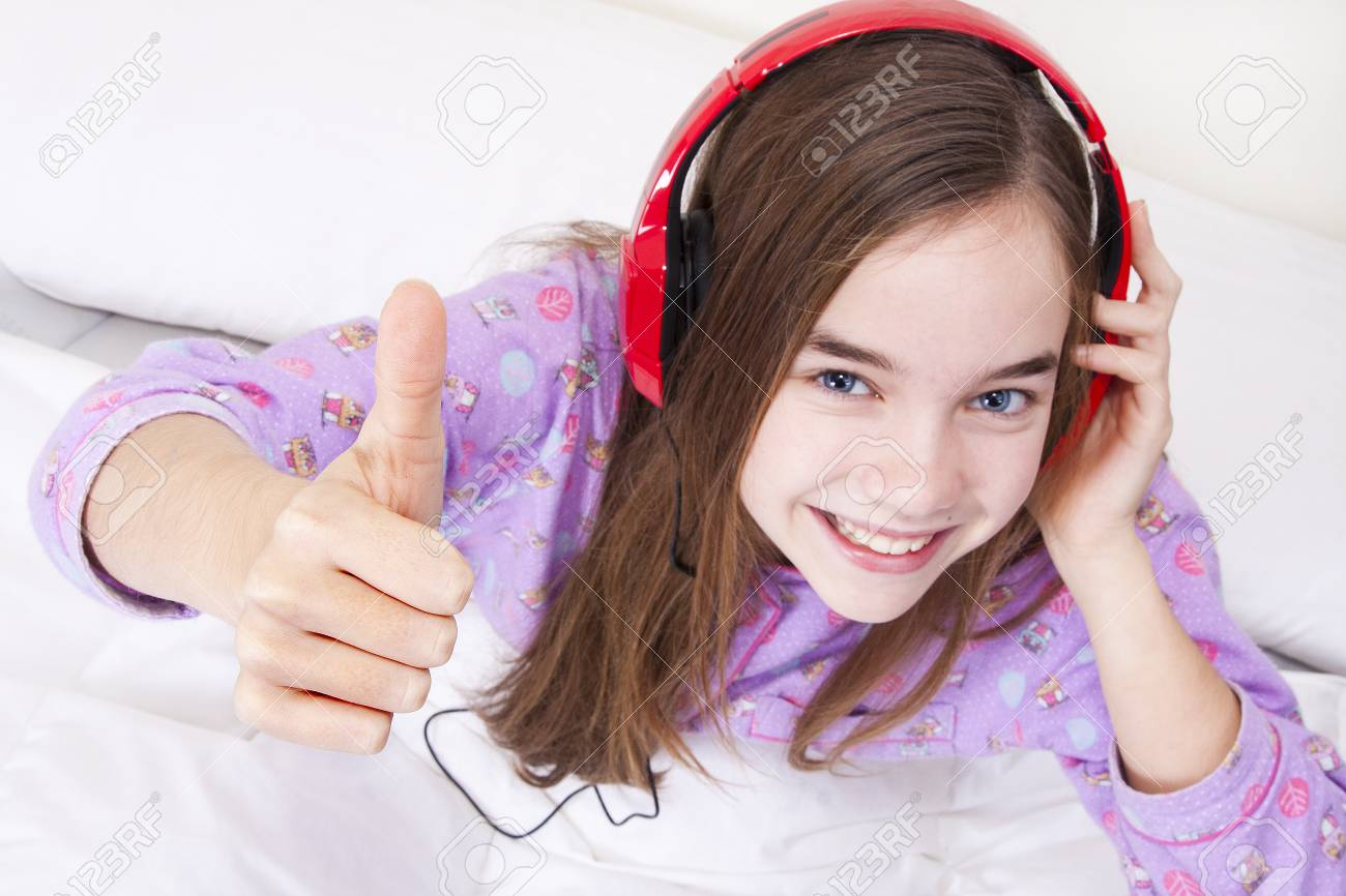 Happy smiling girl with headphones listening to music Stock Photo - 25060269