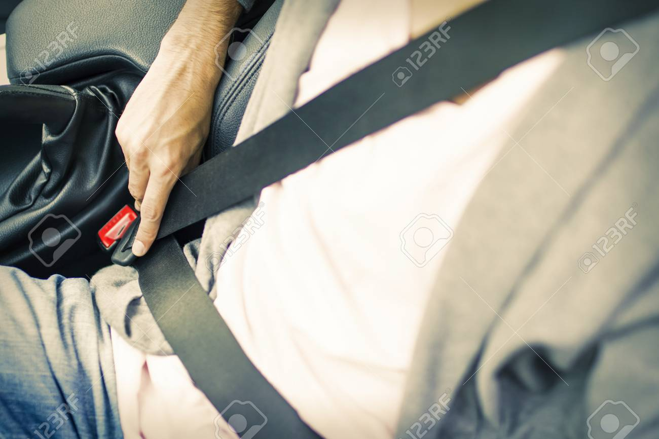 A man's hand fastening the car seatbelt - 90156761
