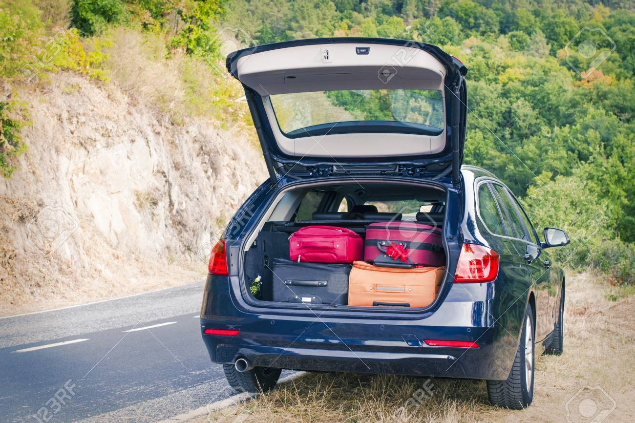 car with trunk loaded with suitcases and luggage - 92563670