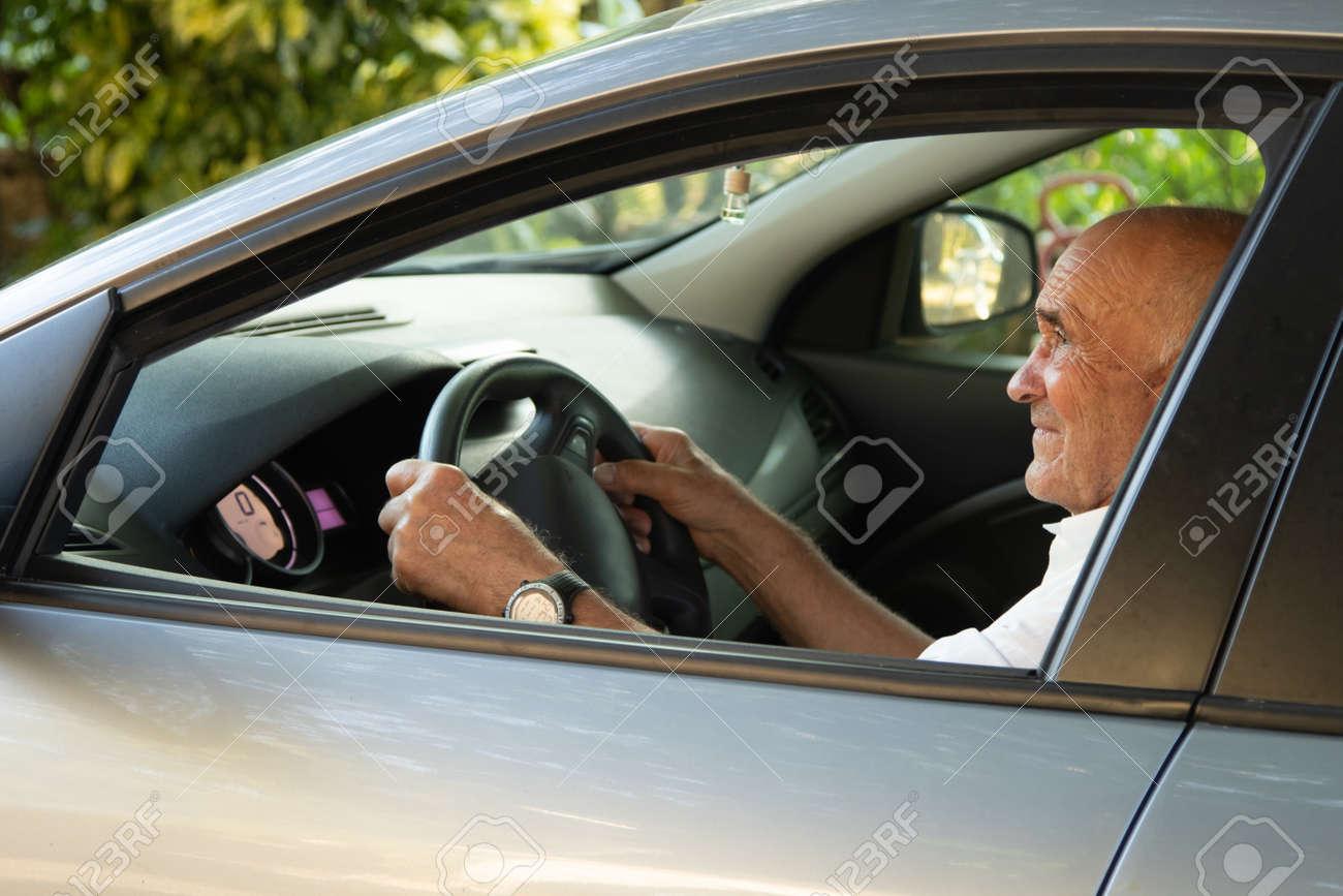portrait of senior male driving car - 156572783