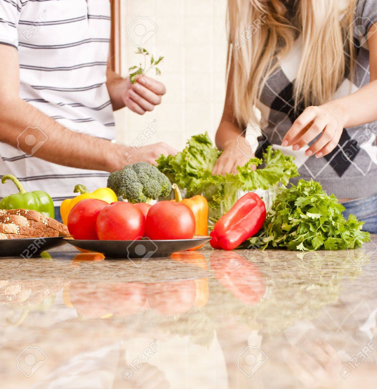 Young couple pick through fresh vegetables behind a kitchen counter. Square shot. Stock Photo - 6249320