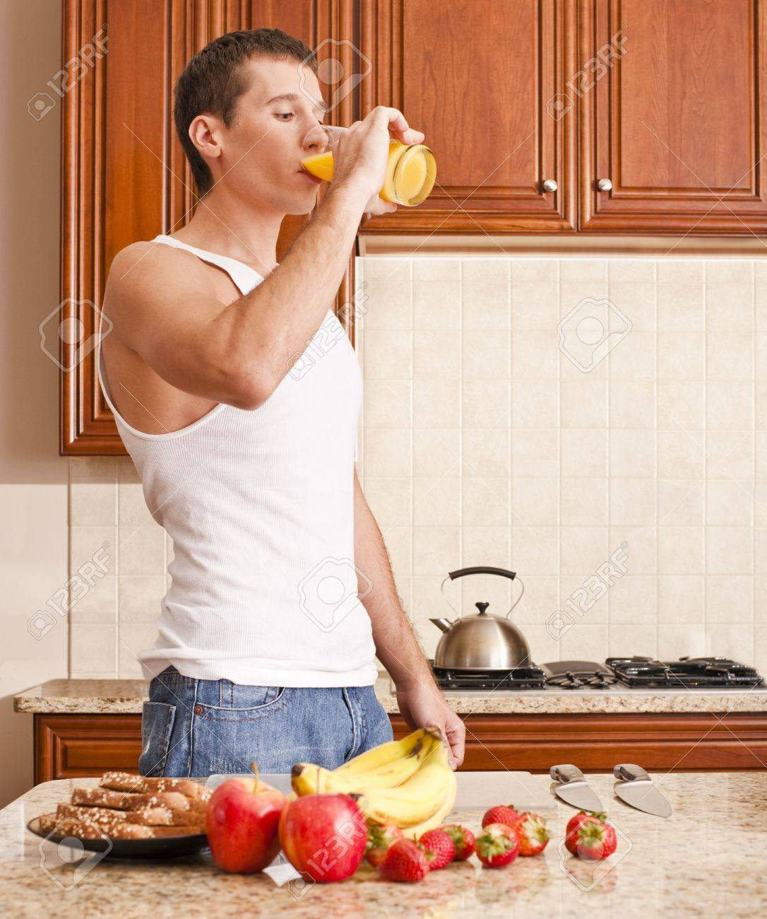 Young man wearing tank top and jeans in kitchen drinking a glass of orange juice. Vertical shot. Stock Photo - 6249270