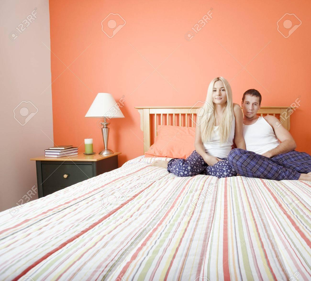 couvre lit jeune Jeune Couple Assis Sur Le Lit Avec Couvre lit écoté. Horizontal  couvre lit jeune