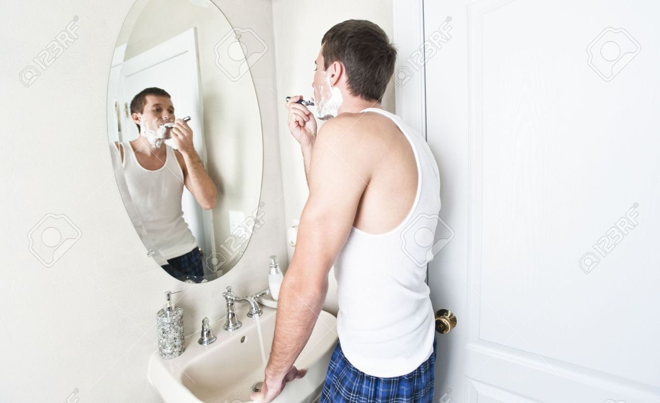 Young man in bathroom looking in the mirror and shaving. Horizontal shot. Stock Photo - 6248637