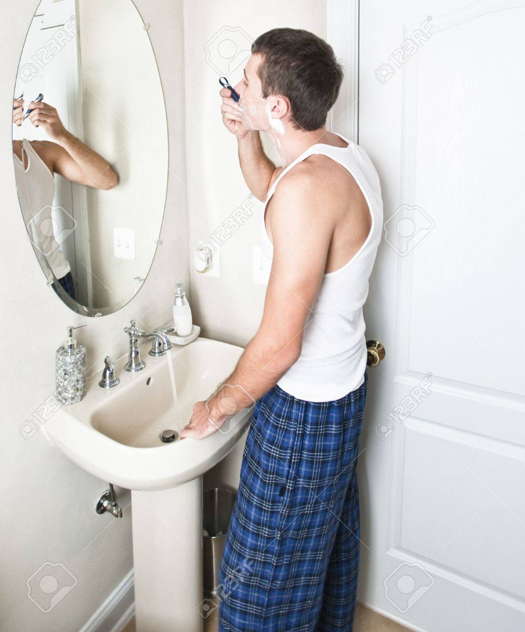 Young man in bathroom looking in the mirror and shaving. Vertical shot. Stock Photo - 6248866