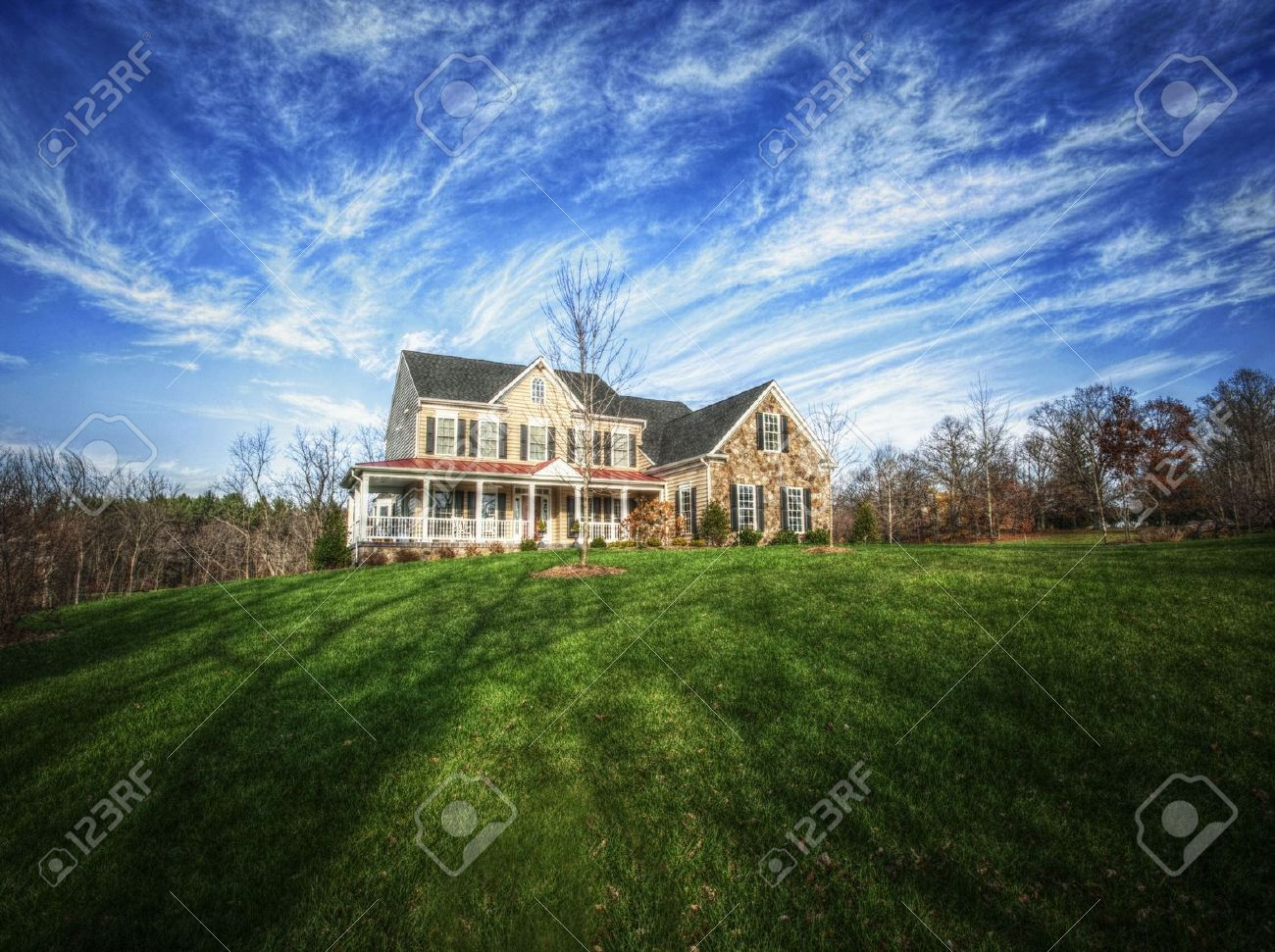 Wide angle view of a traditional home and large yard, with blue sky and cirrus clouds. Horizontal format. Stock Photo - 6249165