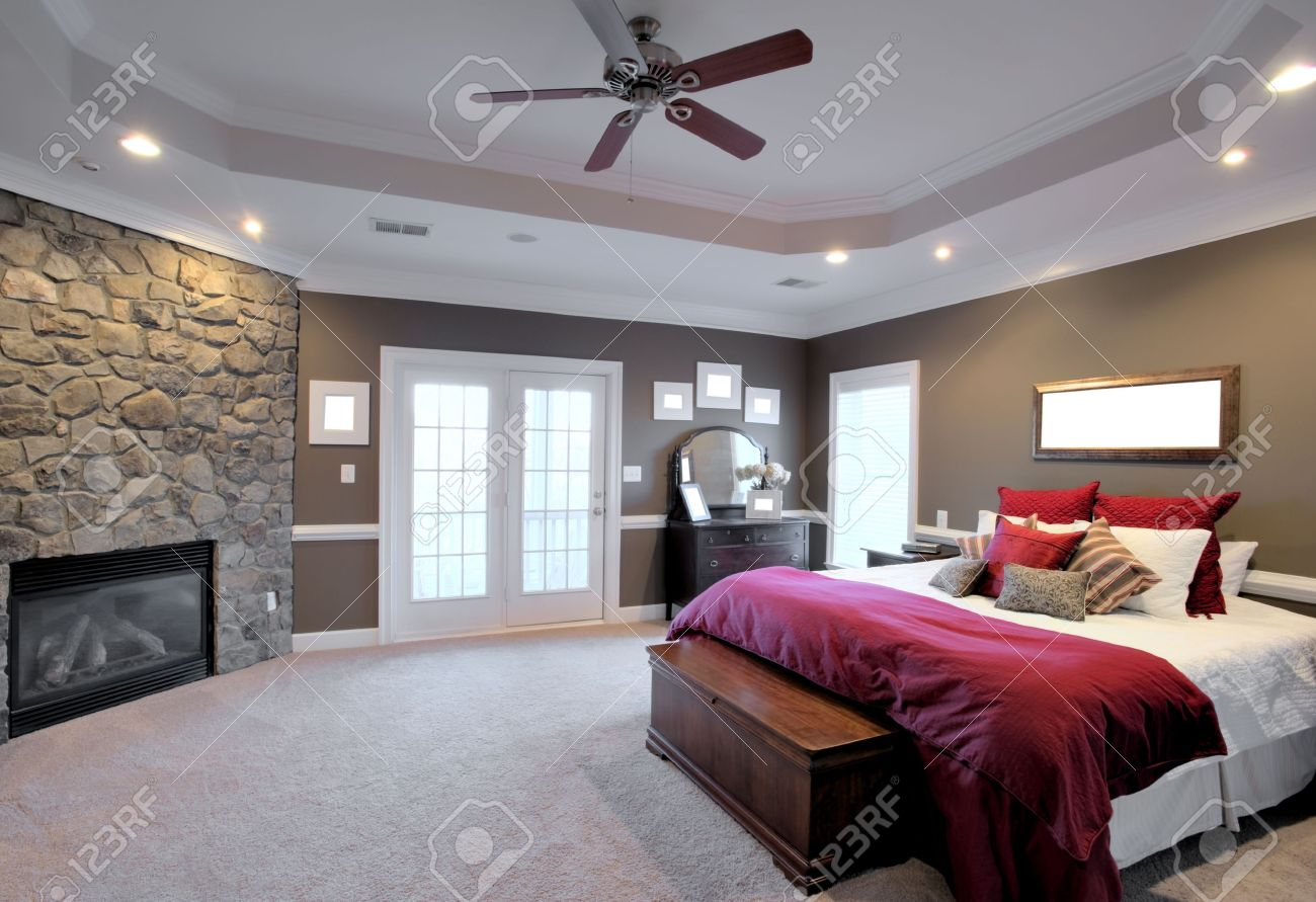 interior of a large modern bedroom with a fireplace and ceiling