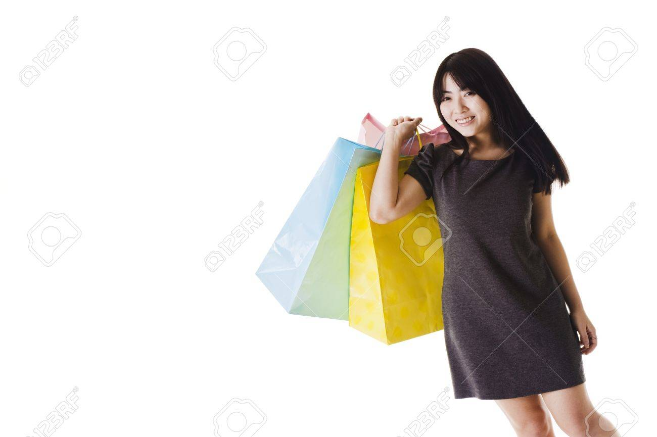 Beautiful Chinese woman with shopping bags in front of a white background. Stock Photo - 11261399