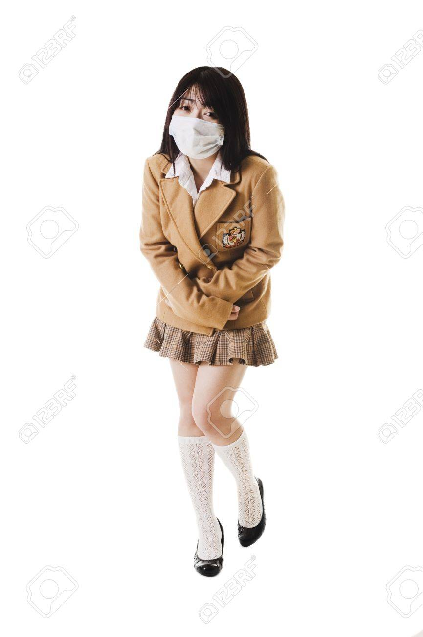 Sick Chinese school girl wearing a face mask holds her stomach in pain. Stock Photo - 11261388