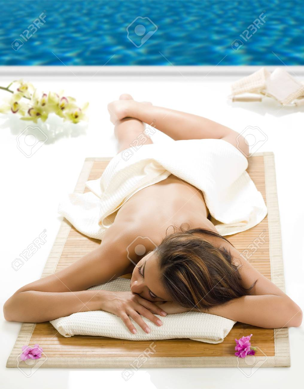 portrait of a beautiful brunette laying down on a wood carpet near a swiming pool Stock Photo - 1665103