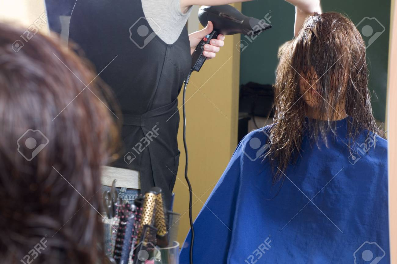 nice girl in a beauty salon while an hair stylist brush and dry her hair Stock Photo - 2584490