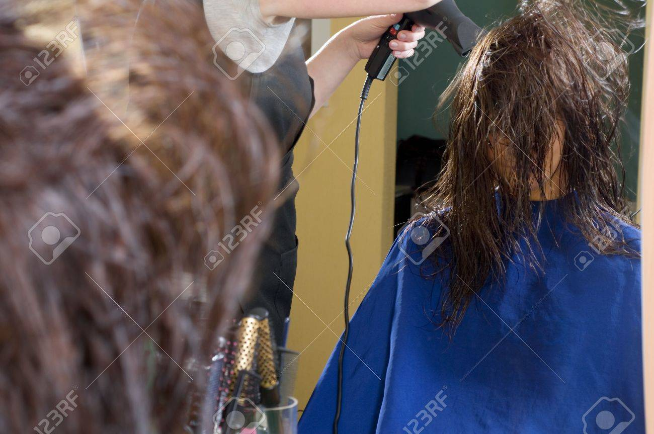 nice girl in a beauty salon while an hair stylist brush and dry her hair Stock Photo - 2584226