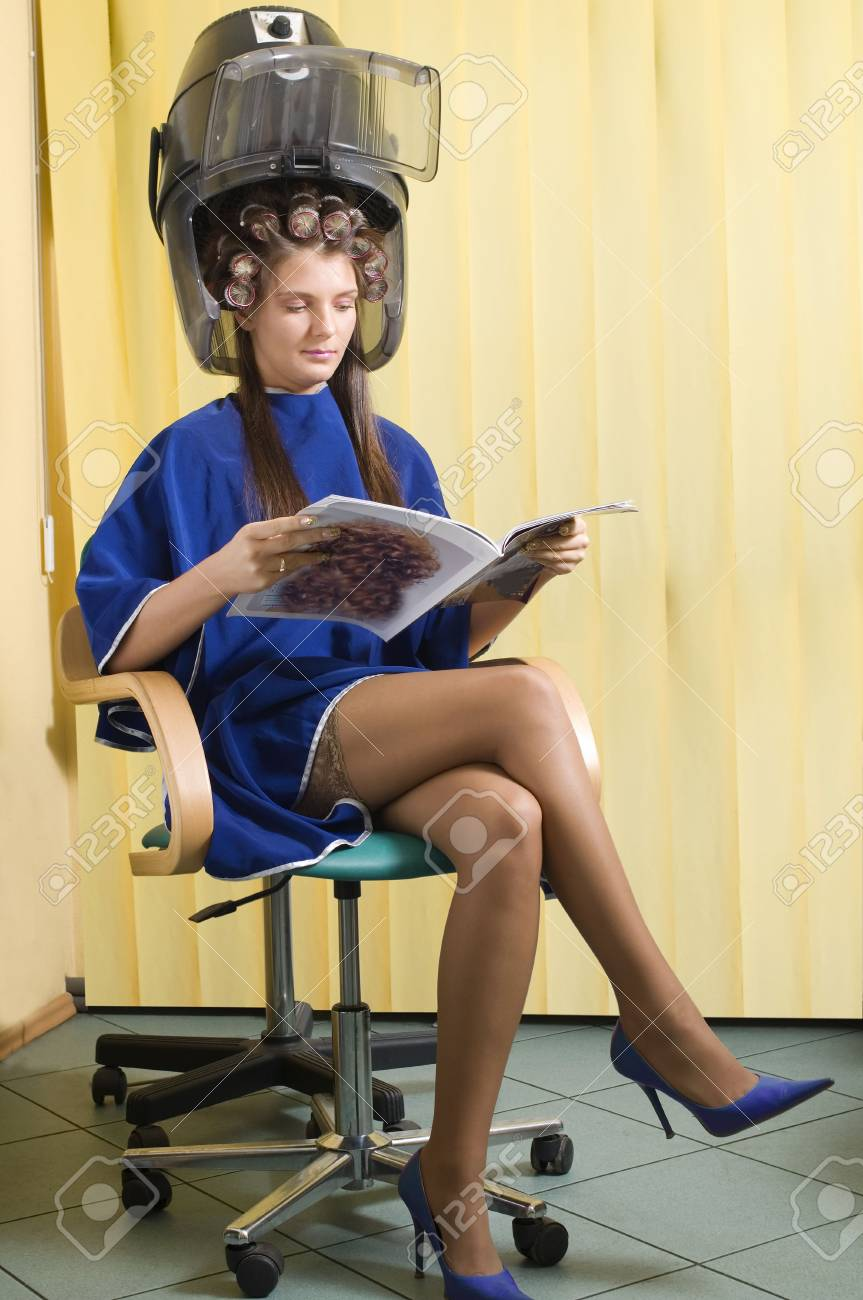 young woman sitting under a hairdryier with roller on head Stock Photo - 2584482