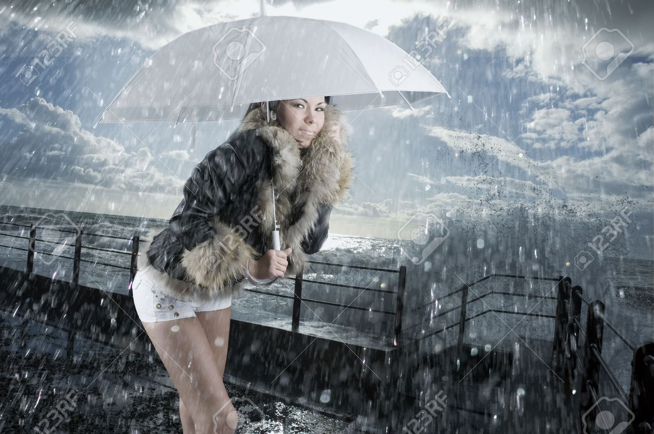 cute brunette near the sea in rough water and under rain Stock Photo - 2729728