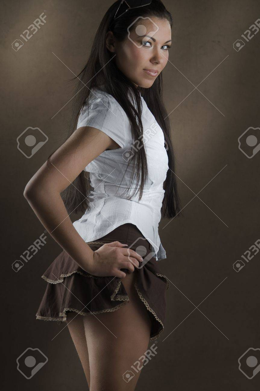 d24a589e74 young and nice girl with white shirt and up brown short skirt Stock Photo -  2743369