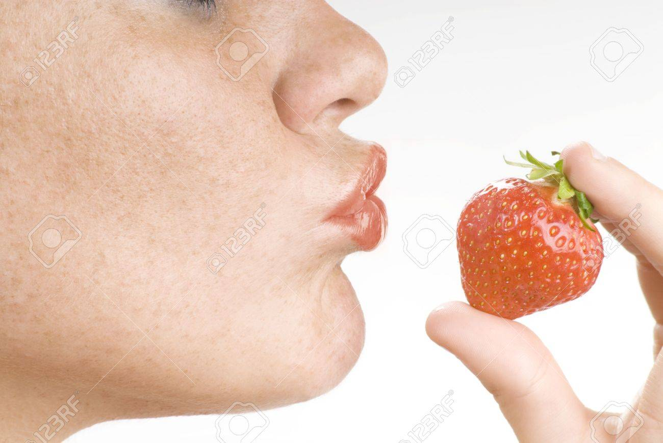 close up of mouth with red lipstick  giving a kiss at the strawberry Stock Photo - 3083798