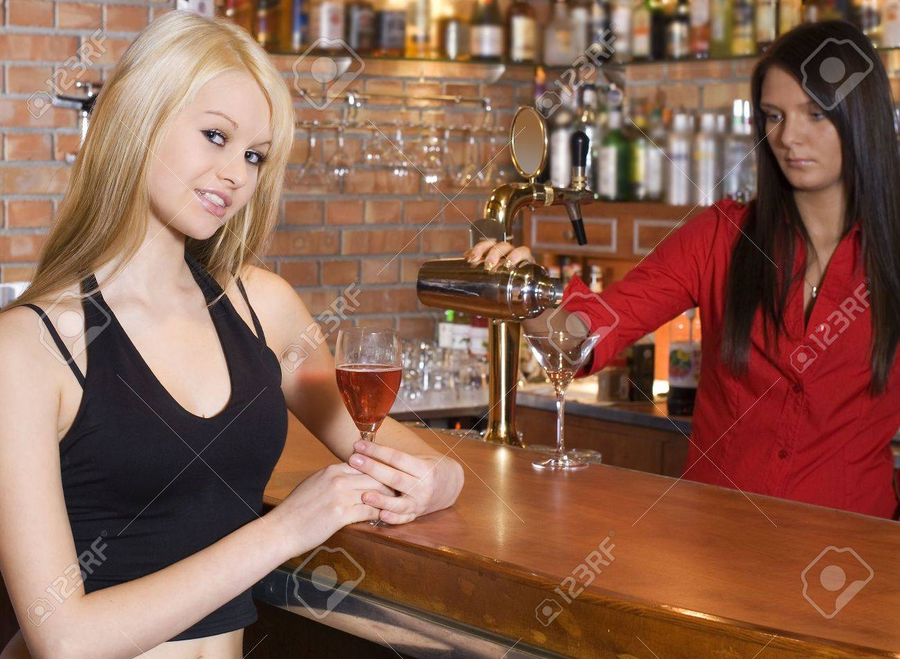 blond girl near the bar with a red cocktail and a barman with shaker focus on the girl Stock Photo - 3307781