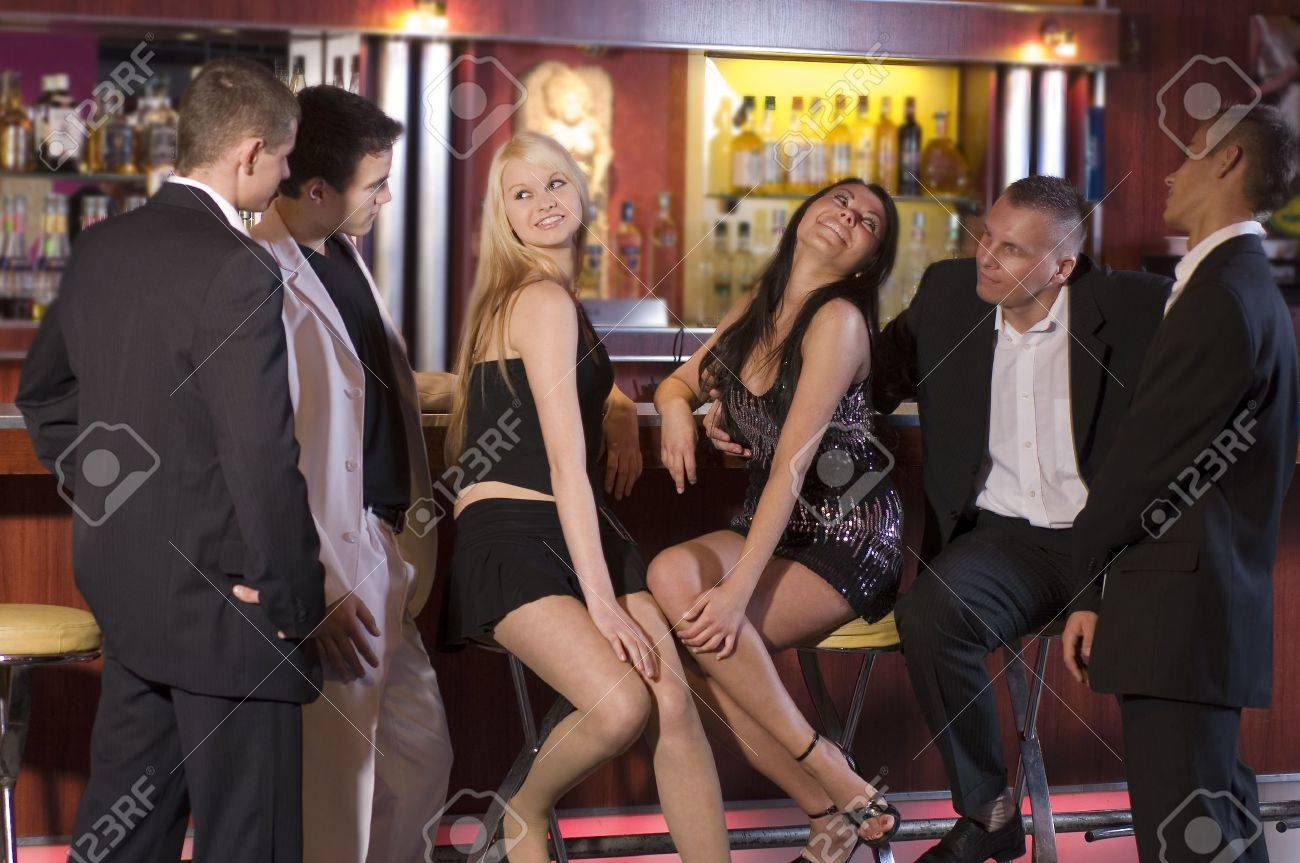A Group Of Young People Sitting Near The Bar Inside A Night Club