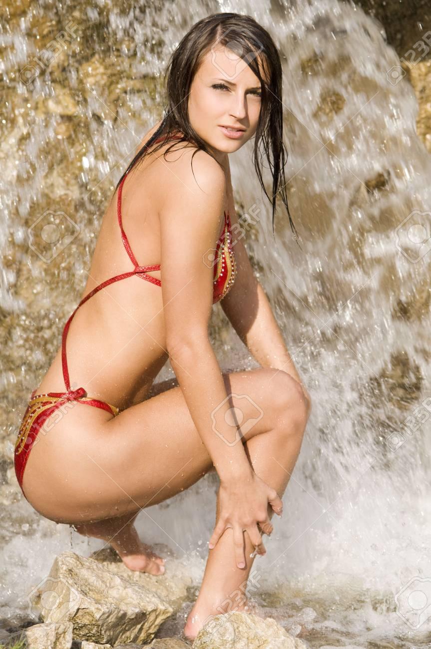 cute brunette in red bikini playing with water near the waterfall Stock Photo - 3430801